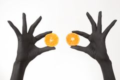 Руки чернокожей женщины держа оранжевые половины Шайки бандитов с ярким вкусным мандарином стоковое фото rf