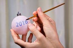 Руки чертежа женщины на шарике рождества Стоковые Фотографии RF