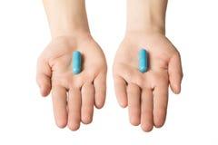 Руки человека давая 2 больших голубых пилюльки выбор делает вашей Спокойная концепция нервов Стоковые Изображения