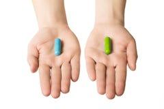 Руки человека давая 2 больших пилюльки Синь и зеленый цвет Сделайте ваш выбор спокойные нервы и здоровье Выберите вашу сторону стоковое фото rf