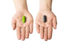 Руки человека давая 2 больших пилюльки черный зеленый цвет Сделайте ваш выбор здоровье или смерть Выберите вашу сторону стоковое фото rf