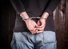 Руки человека в наручниках стоковое изображение