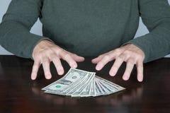 Руки человека готовые для того чтобы уловить пачку долларов Стоковые Изображения