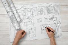 Руки человека держа карандаш над планом чертежа в взгляд сверху Стоковое Фото
