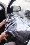Руки человека извлекая старый фильм окна автомобиля Стоковые Изображения RF