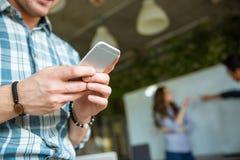 Руки человека используя мобильный телефон пока его спорить партнеров Стоковые Фотографии RF