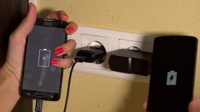 Руки человека и женщины держат поручая умные телефоны соединенный к стенной розетке closeup сток-видео
