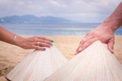 Руки человека и женщины с кольцом, въетнамскими национальными шляпами, Азией, руками на шляпах Стоковая Фотография RF