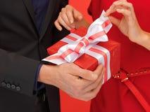 Руки человека и женщины с подарочной коробкой Стоковые Изображения