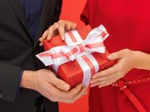 Руки человека и женщины с подарочной коробкой Стоковое Фото