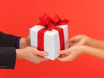руки человека и женщины с подарочной коробкой Стоковые Изображения RF
