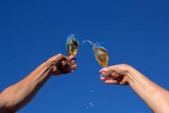 Руки человека и женщины clink рюмки сверкная белого вина стоковые фотографии rf