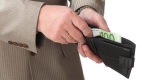 Руки человека кладя банкноты евро в бумажник Стоковая Фотография