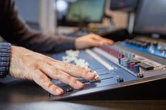 Руки человека на регулировать консоль продукции Стоковые Фото