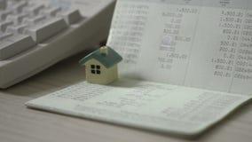 Руки человека работают с сберегательным счетом книги банка и концепцией банковской книжки на предъявителя небольшого дома для ипо акции видеоматериалы