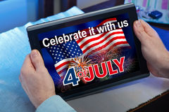 Руки человека смотря в сети место с информацией 4-ое июля Стоковое Изображение