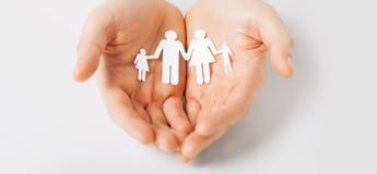 Руки человека с бумажной семьей человека Стоковое фото RF
