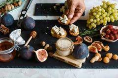 Руки шеф-повара варя bruschetta сыра, смокв и меда Взбрызните с семенами сезама Сырцовые ингредиенты для варить здоровые закуски, стоковые изображения
