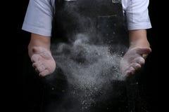 Руки шеф-повара в муке на черной предпосылке хлоп с мукой печь хлеб и и делать пиццу или макаронные изделия стоковая фотография rf