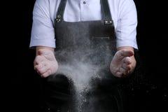 Руки шеф-повара в муке на черной предпосылке хлоп с мукой печь хлеб и и делать пиццу или макаронные изделия стоковое фото rf