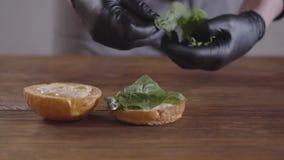 Руки шеф-повара в черных перчатках кухни делая конец-вверх бургера Повар кладя листья базилика на one piece a видеоматериал