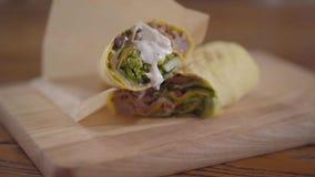 Руки шеф-повара в черных перчатках кухни делая конец-вверх shawarma Повар кладя наполовину shawarma с соусом на его видеоматериал