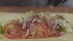 Руки шеф-повара в черных перчатках кухни делая конец-вверх shawarma Повар кладя сочное мясо на томаты и лук дальше акции видеоматериалы
