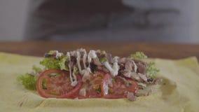Руки шеф-повара в черных перчатках кухни делая конец-вверх shawarma Рт-моча соус полит на завалке Вкусный сток-видео