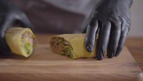 Руки шеф-повара в черных перчатках кухни делая конец-вверх shawarma Вырезывание повара свернуло shaurma на 2 частях и акции видеоматериалы