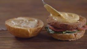 Руки шеф-повара делая конец-вверх бургера Повар кладя расплавленный сыр на котлету, куски томата и листья базилика видеоматериал