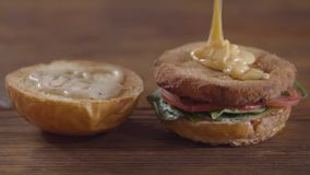 Руки шеф-повара делая конец-вверх бургера Повар льет очень вкусный соус на котлете Вкусное приготовление пищи сток-видео
