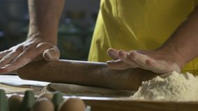Руки шеф-повара подготавливая тесто для пиццы на таблице в кухне HD 100fps сток-видео