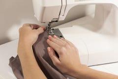 Руки шить на белой ткани коричневого цвета машины Стоковая Фотография RF