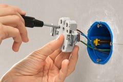 Руки электрика при отвертка устанавливая выключатель Стоковая Фотография