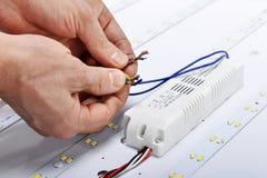 Руки электрика соединяют провода лампы приведенной Стоковое Фото
