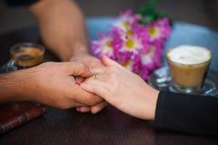 Руки любовников на таблице Стоковое Фото