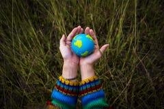 Руки людей придавая форму чашки глобус заботят окружающая среда Стоковые Изображения RF