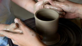 Hands of two people create pot, potter`s wheel. Teaching pottery Stock Footage