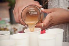 Руки яблочного сока женщины лить в пластичных чашках Стоковая Фотография
