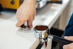 Руки Barista держа portafilter и кофе tamper делающ кофе эспрессо стоковые изображения
