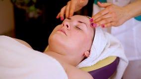 Руки cosmetologist в массаже кругового движения щеки, брови и лоб Лож клиента ослабленные на видеоматериал