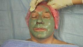 Руки cosmetologist извлекают маску грязи из стороны человека s с пусковой площадкой хлопка видеоматериал