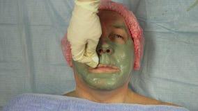 Руки cosmetologist извлекают маску грязи из стороны человека s с пусковой площадкой хлопка сток-видео