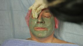Руки cosmetologist извлекают маску грязи из человека акции видеоматериалы
