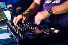 Руки DJs играя на профессиональной доске и смесителе с компьтер-книжкой Стоковое фото RF