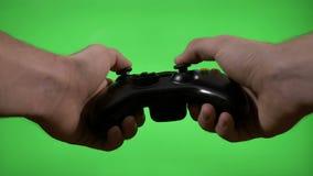 Руки gamer используя регулятор игры для того чтобы сыграть взаимодействующую игру на зеленом ключе chroma экрана - акции видеоматериалы