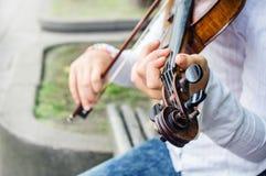 Руки Girl's на строках скрипки и перечень скрипки с колышками стоковое изображение