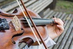 Руки Girl's на строках скрипки стоковые фотографии rf