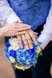 Руки groom и невесты на букете свадьбы Стоковая Фотография