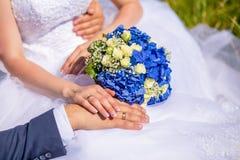 Руки groom и невесты на букете свадьбы Стоковое Фото